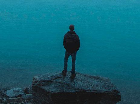 man standing on a rock near water