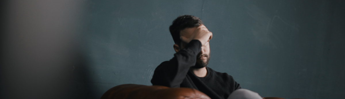 man with migraine holding head in pain
